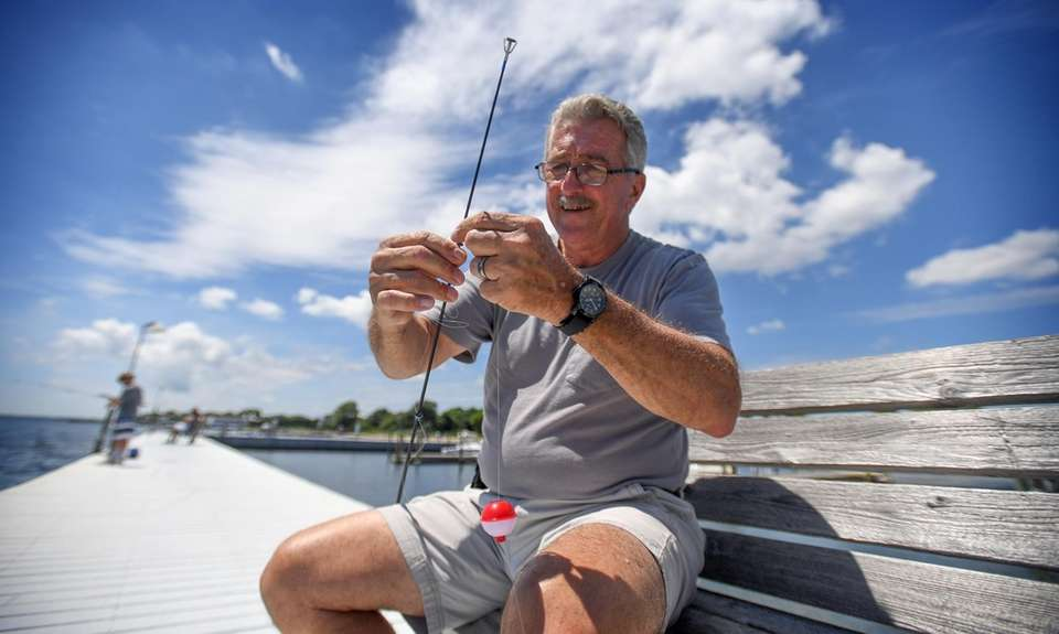 Ralph Gloria of Sayville strings his fishing pole