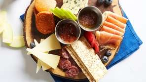 Mixed board of cured meats and cheeses at