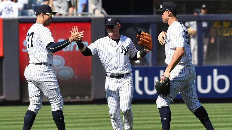 The Yankees' Giancarlo Stanton, left, Clint Frazier, center