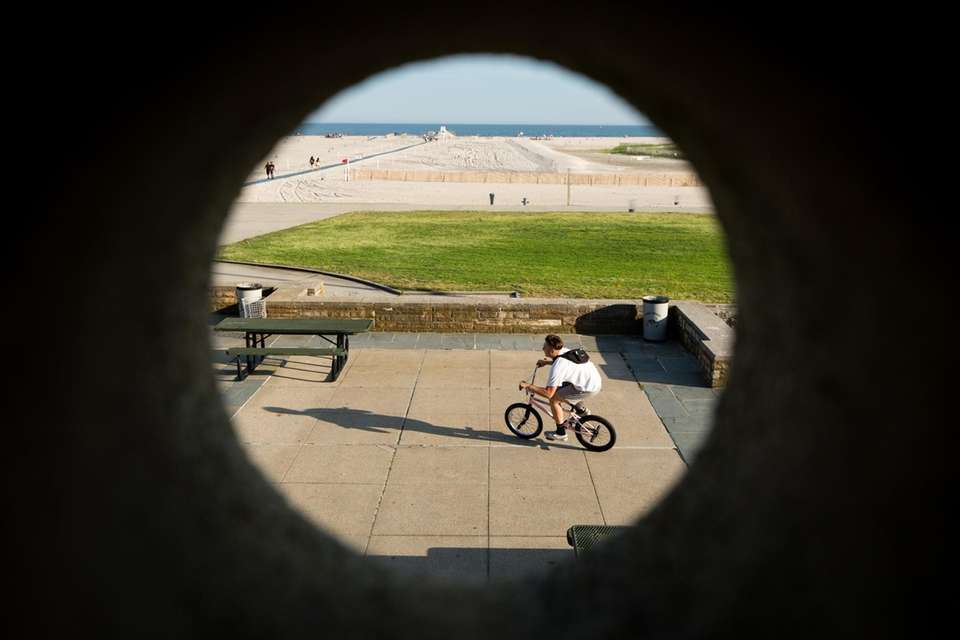 A cyclist rides past the West Bathhouse at