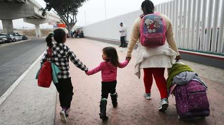 A migrant mother walks with her two daughters