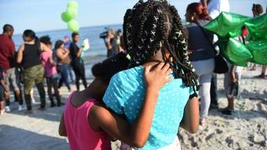 Two young girls embrace each other while family