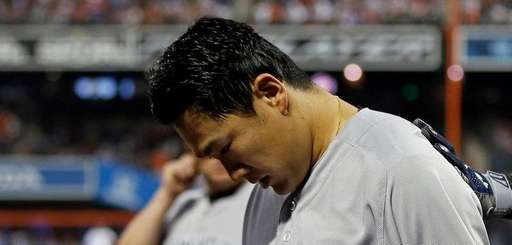Yankees pitcher Masahiro Tanaka is patted on the