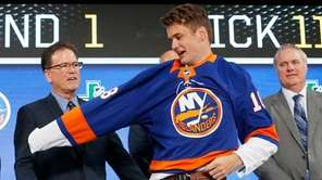 Oliver Wahlstrom puts on an Islanders jersey after