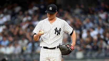 Sonny Gray looking at the ball in the
