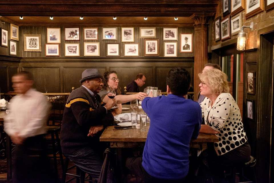 Patrons sip wine and chat at one of