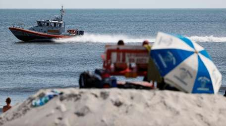 A police search boat scans the shore in