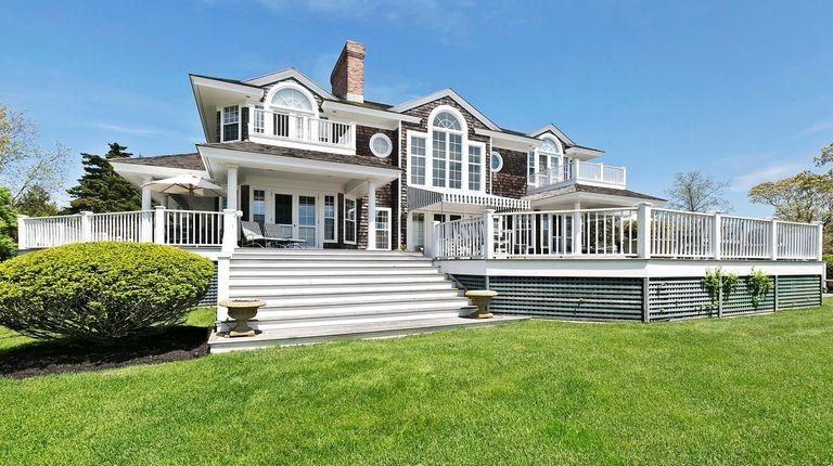 The six-bedroom, shingled house has a wraparound porch,