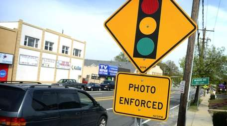 A sign notifies drivers of a red-light camera