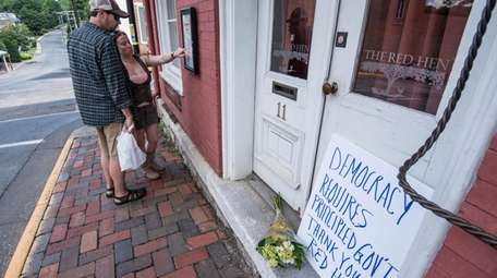 Passersby examine the menu at the Red Hen