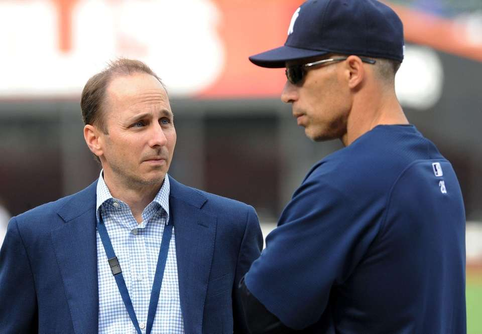 Yankees GM Brian Cashman, at left with manager