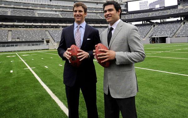 Giants quarterback Eli Manning poses with Jets quarterback