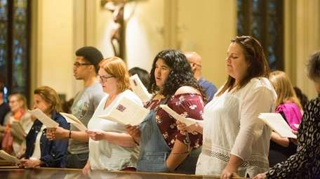 Parishioners join in song during the Immigration Through