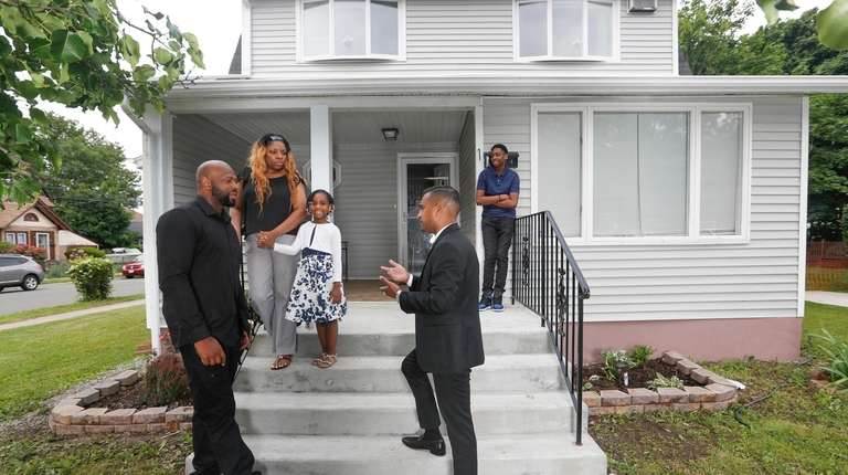 Real estate agent Christopher Bacchus, center, visits with