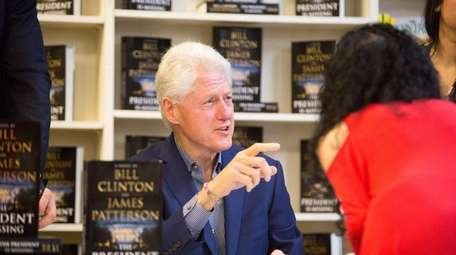 Former President Bill Clinton signs copies of his