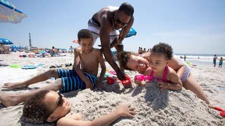 Trae Richards, 5, left, gets buried in the