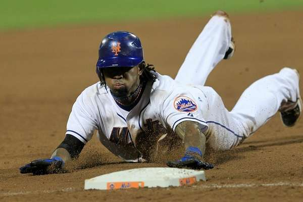 Jose Reyes slides into third base with a