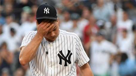 Yankees starting pitcher Sonny Gray reacts after giving