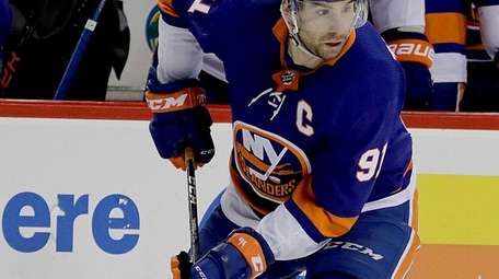 Islanders center John Tavares moves the puck to