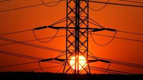 The sun rises behind power lines in Melville,