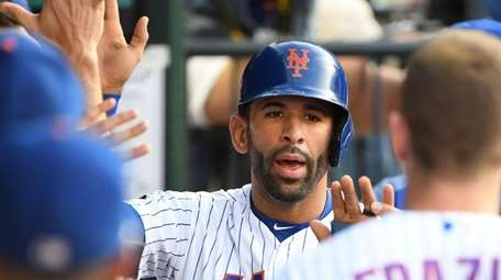 Jose Bautista is greeted in the Mets' dugout