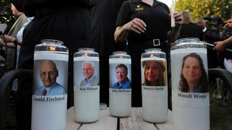 Photos of five journalists adorn candles during a