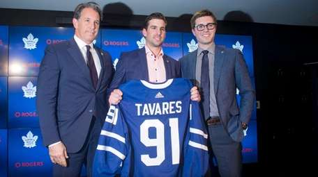 John Tavares poses with Maple Leafs president Brendan