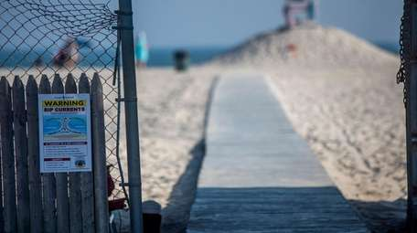 Rip current warnings are posted at the beach