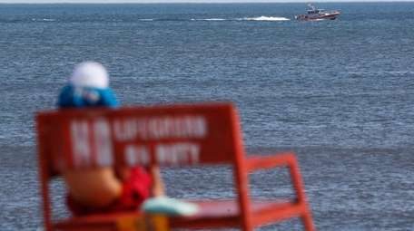 Search boats scan the shore at Long Beach
