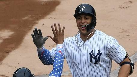 New York Yankees center fielder Aaron Hicks greets