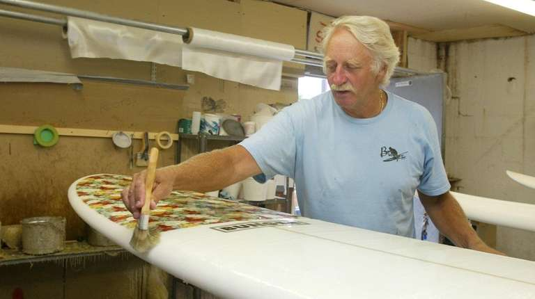 Charlie Bunger hot coats a 10-foot surfboard at