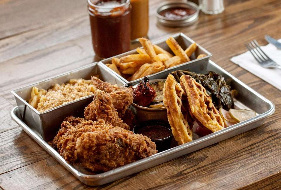 Fried chicken served with sides of collards, fries,