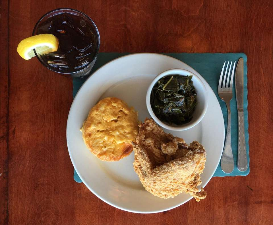 Fried chicken with a biscuit and collards, served