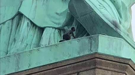 A person scales the Statue of Liberty in