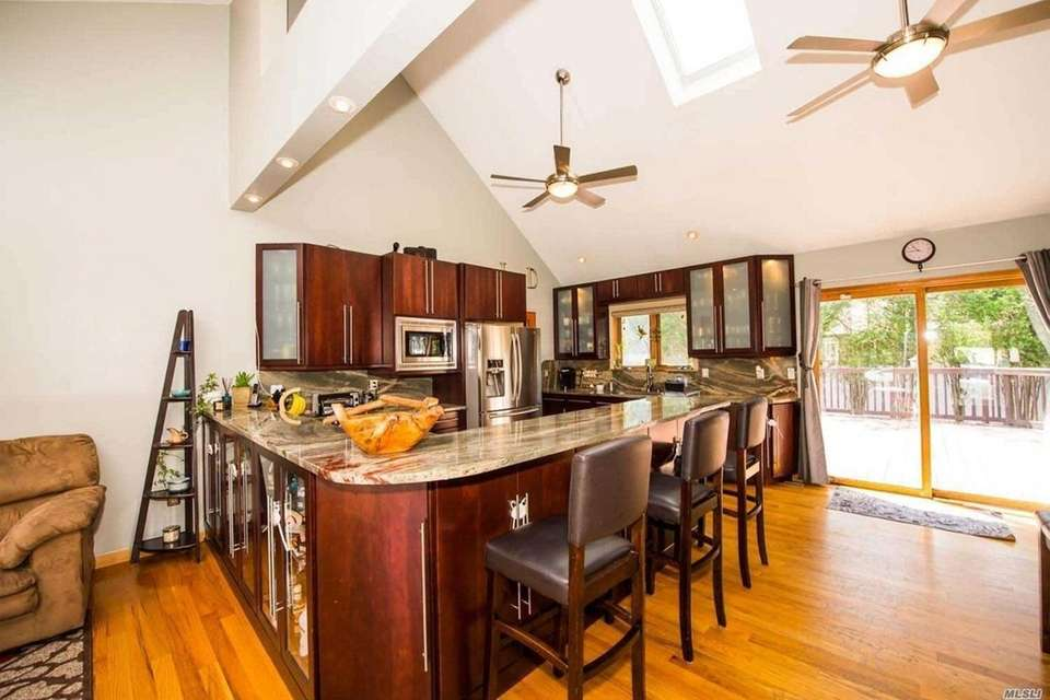 The kitchen features a breakfast bar, vaulted ceilings