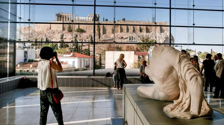 Visitors to Athens' Acropolis Museum view the ancient