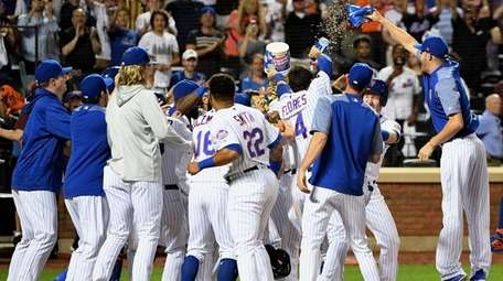 Mets players mob Jose Bautista at home plate
