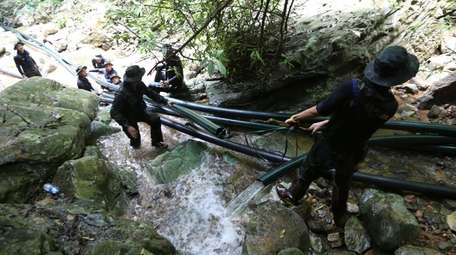 Thai soldiers divert water from the cave where