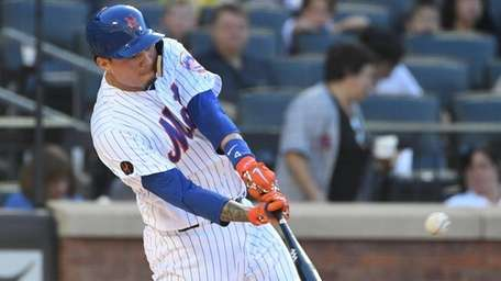 Mets first baseman Wilmer Flores singles against the