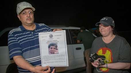 Luis Germosen holds a phot of his missing
