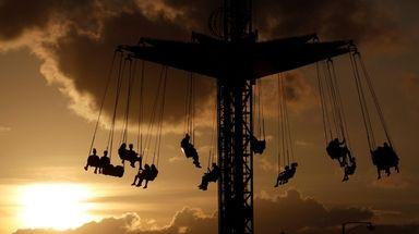 The sun begins to set behind fairgoers hanging