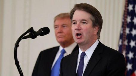 President Donald Trump listens as Judge Brett Kavanaugh,