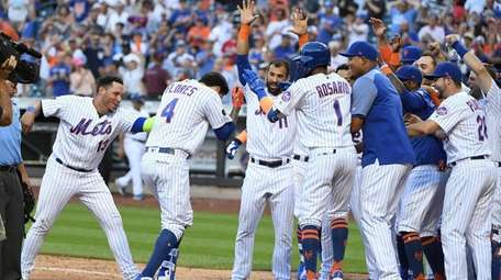 Mets pinch-hitter Wilmer Flores is mobbed at home