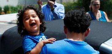 Ever Reyes Mejia of Honduras carries his 3-year-old