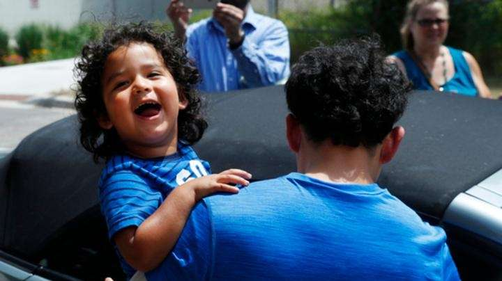 Ever Reyes Mejia of Honduras carries his 3-year-old