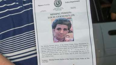 Luis Germosen holds a police poster of his