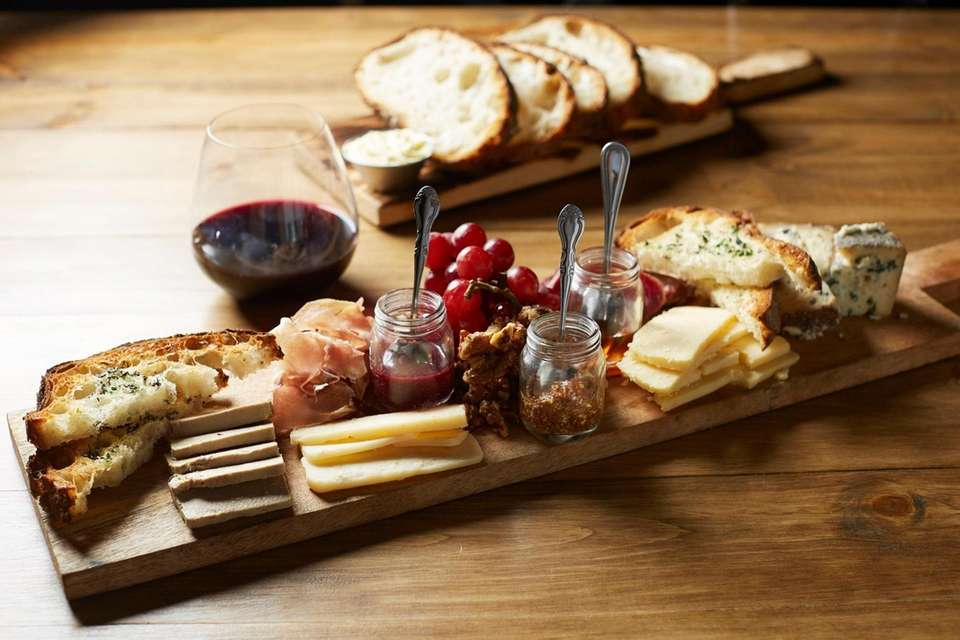A charcuterie boards combines artisanal cheeses and cured