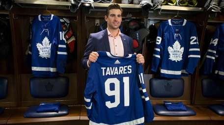 John Tavares holds up a Maple Leafs jersey