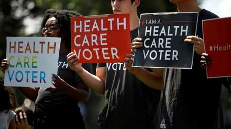 Demonstrators hold signs as Democratic leaders speak with