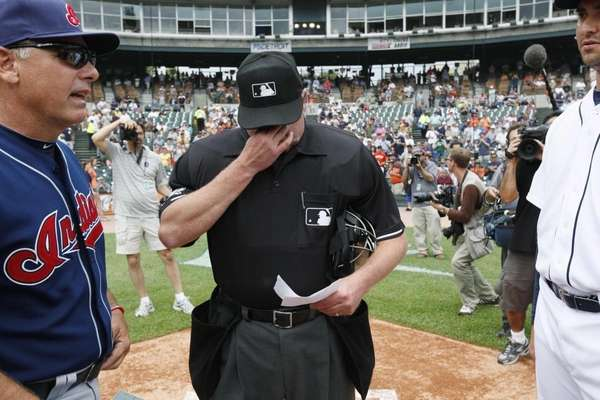 Home plate umpire Jim Joyce wipes tears during